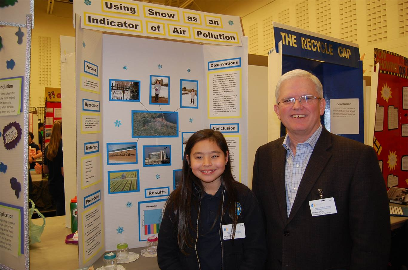 Kayla Leon, a Grade 5 student at Annunciation of Our Lord Catholic Elementary School, shown here with Chairperson Patrick Daly, used snow to test air pollution.